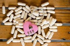 Розовый ключ для всех замков на лекарстве капсулы стоковые изображения rf