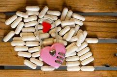 Розовый ключ для всех замков на лекарстве капсулы стоковые изображения