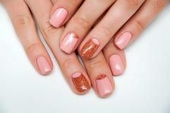 Розовый маникюр золота на коротких квадратных ногтях Стоковая Фотография