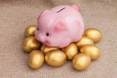Розовый подъем копилки на куче золотого пасхального яйца Стоковое фото RF