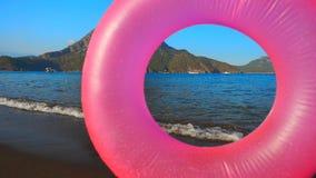 Розовый раздувной круг на пляже акции видеоматериалы