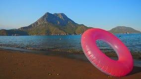 Розовый раздувной круг на пляже видеоматериал