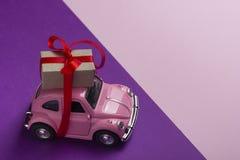 Розовый ретро автомобиль игрушки поставляя подарочную коробку на пастельной предпосылке Взгляд сверху Стоковые Изображения