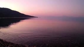 Розовый свет рассвета на спокойном заливе Gulf of Corinth