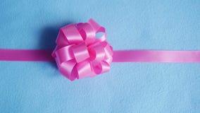 Розовый смычок подарка на голубой предпосылке ткани стоковые фотографии rf