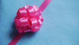 Розовый смычок подарка на голубой предпосылке ткани стоковая фотография rf