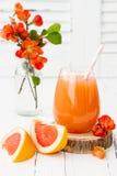 Розовый сочный домодельный коктеиль грейпфрута с спиртом над старым винтажным деревянным столом Стоковое Фото