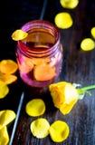 Розовый стеклянный опарник с желтыми лепестками розы Стоковая Фотография