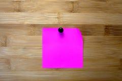 Розовый стикер на деревянной предпосылке Стоковые Фото