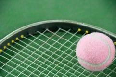 Розовый теннисный мяч на ракетке Стоковые Фотографии RF