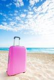 Розовый чемодан на пляже Стоковое фото RF