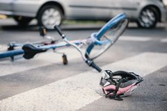 Розовый шлем и голубое ` s ребенк велосипед на пешеходном переходе после inc стоковое изображение