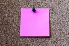 Розовый штырь бумаги примечания на пробковой доске Стоковое Изображение