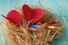 2 розовых бумажных сердца в малом гнезде на деревянной предпосылке Стоковое фото RF