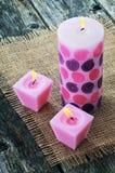 3 розовых горящих свечи на джуте предпосылки Стоковое Изображение