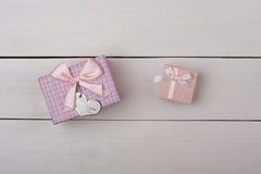 2 розовых подарка с смычками на белом деревянном столе Стоковые Изображения