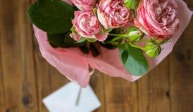 Розы в вазе с конвертом на деревянной серой предпосылке стоковая фотография rf