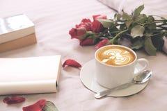 Розы кофе Latte цветут и пустая книга на кровати Стоковое Фото