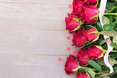 Розы красного цвета зацветая на древесине Стоковая Фотография