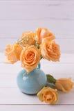 Розы персика цветут в голубой вазе на белой деревянной предпосылке Стоковое Фото