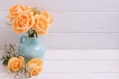 Розы персика цветут в голубой вазе на белой деревянной предпосылке Стоковое фото RF