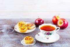 Розы чашки чаю и яблока сформировали булочки на деревенском деревянном столе Стоковое фото RF