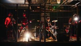 Рок-группа выполняет на этапе в клетке сток-видео