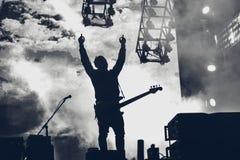 Рок-группа выполняет на этапе Гитарист играет solo Силуэт  стоковые изображения rf