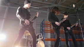 Рок-группа имея повторение Гитаристы в черных одеждах играя их части и барабанщика на предпосылке стоковое изображение