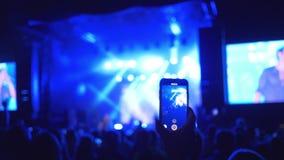 Рок-концерт, всход аудитории вентиляторов на выполнять мобильного телефона музыкальной группы на ярко освещении вечером видеоматериал
