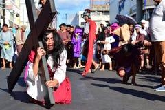 Роль Иисуса Христоса плача в боли и агонии нося тяжелый деревянный крест на улице Стоковые Фотографии RF
