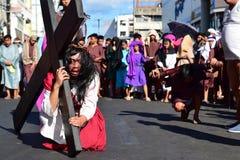 Роль Иисуса Христоса плача в боли и агонии нося тяжелый деревянный крест на улице Стоковое Изображение RF