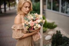 Романтичная белокурая женщина держа обнажённый бежевый букет цветков стоковые фотографии rf