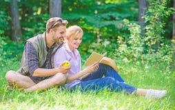 Романтичная дата на зеленом луге Пары в любов тратят книгу чтения отдыха Романтичные студенты пар наслаждаются отдыхом с стоковое фото rf