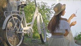 Романтичная женщина брюнет в длинной белой юбке, блузке и соломенной шляпе сидит на речном береге около ее велосипеда города и акции видеоматериалы
