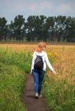 Романтичная женщина идя в поле зеленой травы, идя в лето Стоковое Изображение RF