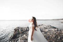 Романтичная красивая невеста в белом платье представляя на море предпосылки Стоковое Изображение