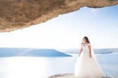 Романтичная красивая невеста в белом платье представляя на море предпосылки Стоковые Изображения
