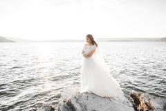 Романтичная красивая невеста в белом платье представляя на море предпосылки Стоковые Фотографии RF