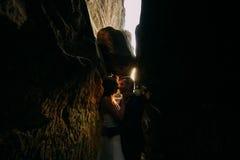 Романтичная красивая невеста и элегантный стильный groom целуя в затмленной расселине утеса backgrounded заходом солнца светя Стоковое фото RF