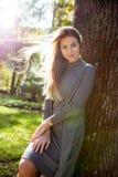 Романтичная молодая женщина носит серое платье, с волосами в представлять ветра Стоковые Изображения