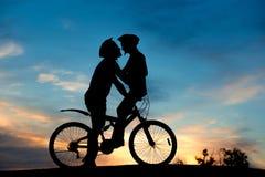 Романтичная пара велосипедистов целует на заходе солнца Стоковая Фотография RF