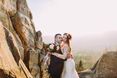 Романтичная пара новобрачных держа один другого в заходе солнца освещает с скалистым ландшафтом как backround Стоковые Изображения
