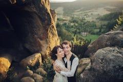 Романтичная пара новобрачных представляя в заходе солнца освещает на величественном roc Стоковые Фото