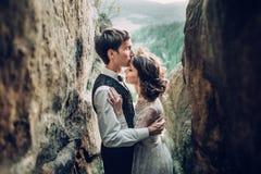 Романтичная пара новобрачных представляя в заходе солнца освещает на величественном roc Стоковое Изображение RF