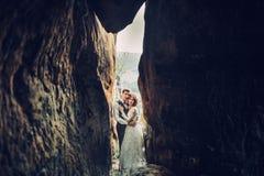 Романтичная пара новобрачных представляя в заходе солнца освещает на величественном roc Стоковая Фотография