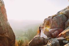 Романтичная пара новобрачных представляя в заходе солнца освещает на величественной скале скалистой горы с сельским взглядом как  Стоковое фото RF
