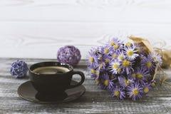 Романтичная предпосылка с чашкой кофе, букетом фиолетовых цветков в бумаге ремесла на сером деревянном столе стоковая фотография