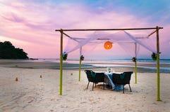 Романтичная роскошная сервировка стола обедающего на тропическом пляже во время Стоковые Фотографии RF