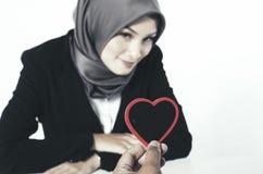 Романтичная рука взгляда держа сердце сделанный от древесины над предпосылкой запачканного и селективного фокуса Стоковые Фото
